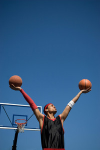 A young basketball player holding up two basketballs in the shape of a V.