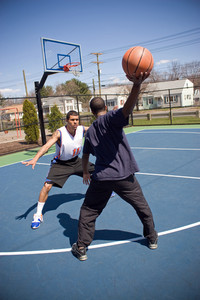 A young basketball player is taunting his opponent with the ball while playing one on one.