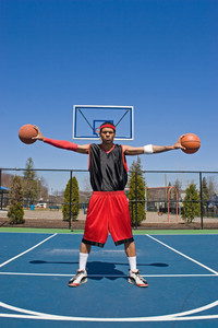 A young basketball player palming two basketballs.