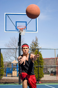 A young basketball player passing the ball across the court.