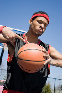 A young basketball player posing with the ball with confidence.