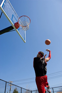 A young basketball player shooting in a hook shot or lay up.