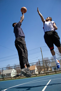 A young basketball player shooting the basketball and his opponent trying to block it.