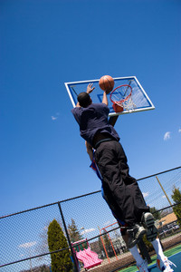 A young basketball player shoots the basketball at the hoop.