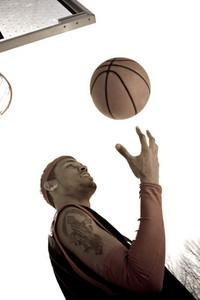 A young basketball player tossing the ball while standing under the hoop.