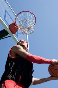 A young basketball player under the rim going for a reverse slam dunk.  Shallow depth of field with stronger focus on the goal.