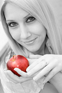 A young blond posing with an apple - black and white with selective color.