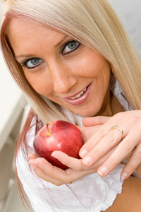A young blond posing with an apple that she is holding in her hand.