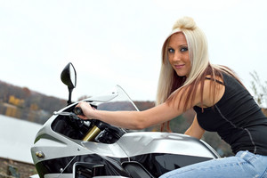 A young blonde woman poses on her motorcycle.