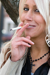 A young blonde woman takes a cigarette break outdoors.