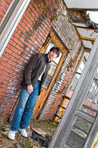 A young brunette man posing outside a worn and abandoned building.