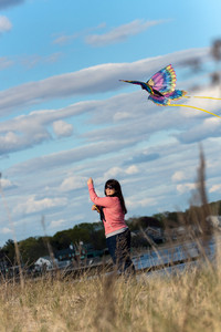 A young brunette woman flies a kite at the beach on a nice day.