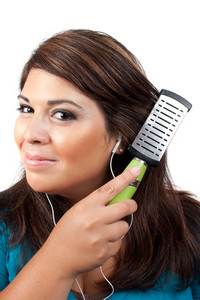 A young brunette woman listening to music while brushing her hair.