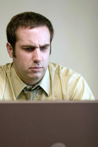 A young business man is looking concerned at what he is seeing on his laptop screen.