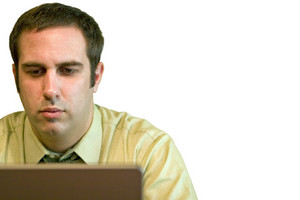 A young business man working from home on his laptop.  Plenty of copy space - image includes clipping path.