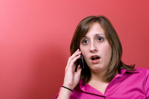 A young business woman just heard something that worries her on her cell phone.