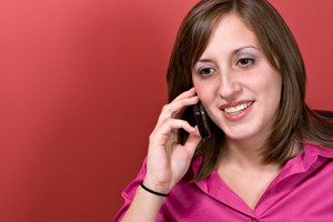 A young business woman talking on her cell phone isolated over a red background.