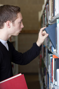A young college aged man looks at a book at the library.