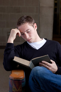 A young college aged man reading a book at the library.