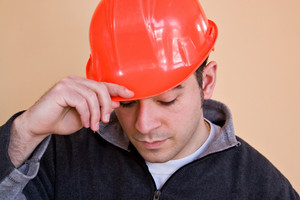 A young construction professional tips putting on his hard hat.