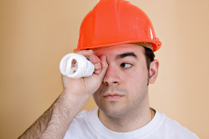 A young construction worker or home builder holding an energy saving compact fluorescent light bulb up to his eye.