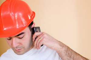 A young construction worker talks on his smartphone.  Plenty of copyspace for your text or images.