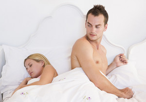 A young couple in bed with the man looking worried