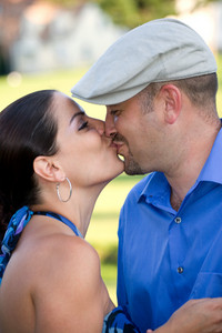 A young couple kissing each other on the lips.