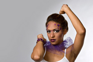 A young dancer with gemstones on her face isolated over a silver backdrop.