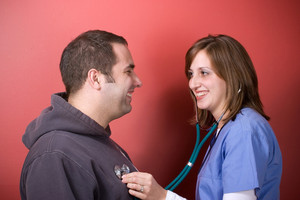 A young doctor or nurse listening to the heartbeat of her patient with her stethoscope during an office visit.