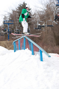 A young freestyle skier grinding down a rail on his skis.