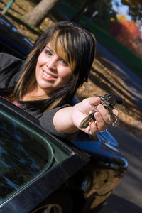 A young girl happily shows off the keys to her new car. Shallow depth of field with focus on the hand.