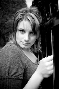 A young girl with highlighted hair posing by a fence in black and white.