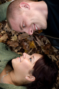 A young happy couple gazing into each others eyes while laying in a pile of leaves.
