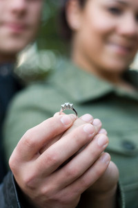 A young happy couple holding a diamond engagement ring.  Shallow depth of field with focus on the ring.
