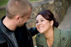 A young happy couple looking fondly at one another outdoors.  Shallow depth of filed with focus in the woman.