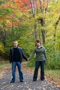 A young happy couple on a path in the woods during Autumn.