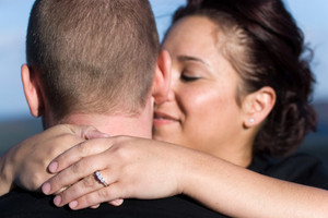A young happy couple that just got engaged.  Shallow depth of field with focus on the diamond engagement ring.