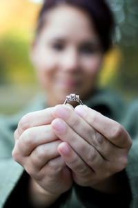 A young happy woman holding a diamond engagement ring.  Shallow depth of field with focus on the ring.