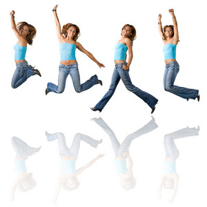 A young Hispanic girl in her early twenties jumping in the air in four different poses with reflections over white.