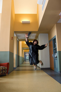 A young Hispanic woman jumps in the air with joy while wearing her cap and gown.  Slight motion blur on the hands and feet.