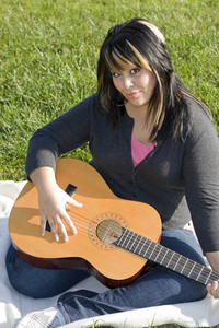 A young hispanic woman playing a guitar while sitting on a blanket in the green grass.  Her hair is highlighted with blonde streaks.