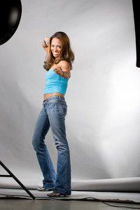 A young hispanic woman posing in a studio setting. A behind the scenes look at the setup using multiple lights with soft boxes and a beauty dish.