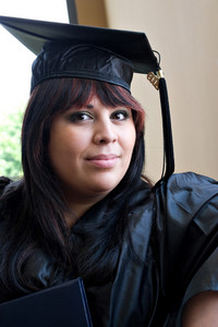 A young hispanic woman wearing her cap and gown on graduation day.