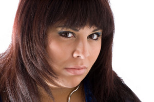 A young Hispanic woman with a fierce look on her face isolated over white.