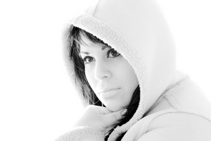 A young hispanic woman with a hood on her head in black and white.