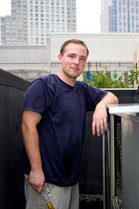 A young HVAC technician working on a rooftop.