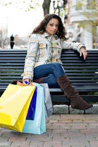 A young Indian woman taking a break on a park bench while out shopping in the city.