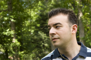 A young Italian man with spiked hair standing in front of a wooded background.