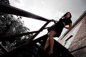 A young lady poses on a rusted old stairway in an urban setting.  Selective color.
